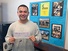 Compass Rose Collaborative participant Carlos showing his paid internship paycheck