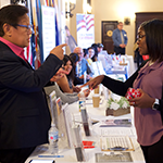 Business Development Loan Officer Terry Gubatan (left) of the South LA BusinessSource Center speaks to a potential client at the early November Entrepreneurship & Financial Literacy Conference
