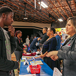 job seeker at the Southeast Los Angeles WorkSource Center job fair May 2, 2019 speaks with Virginia Montano (right), a representative from truck driver services company ProDrivers