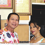 Glady Uy, owner of Super Donut House in Hollywood, and his wife behind the counter of his business