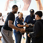 Former LA Laker Metta World Peace greets a YouthSource participant while EWDD General Manager Jan Perry looks on with EWDD Youth Operations Team staff